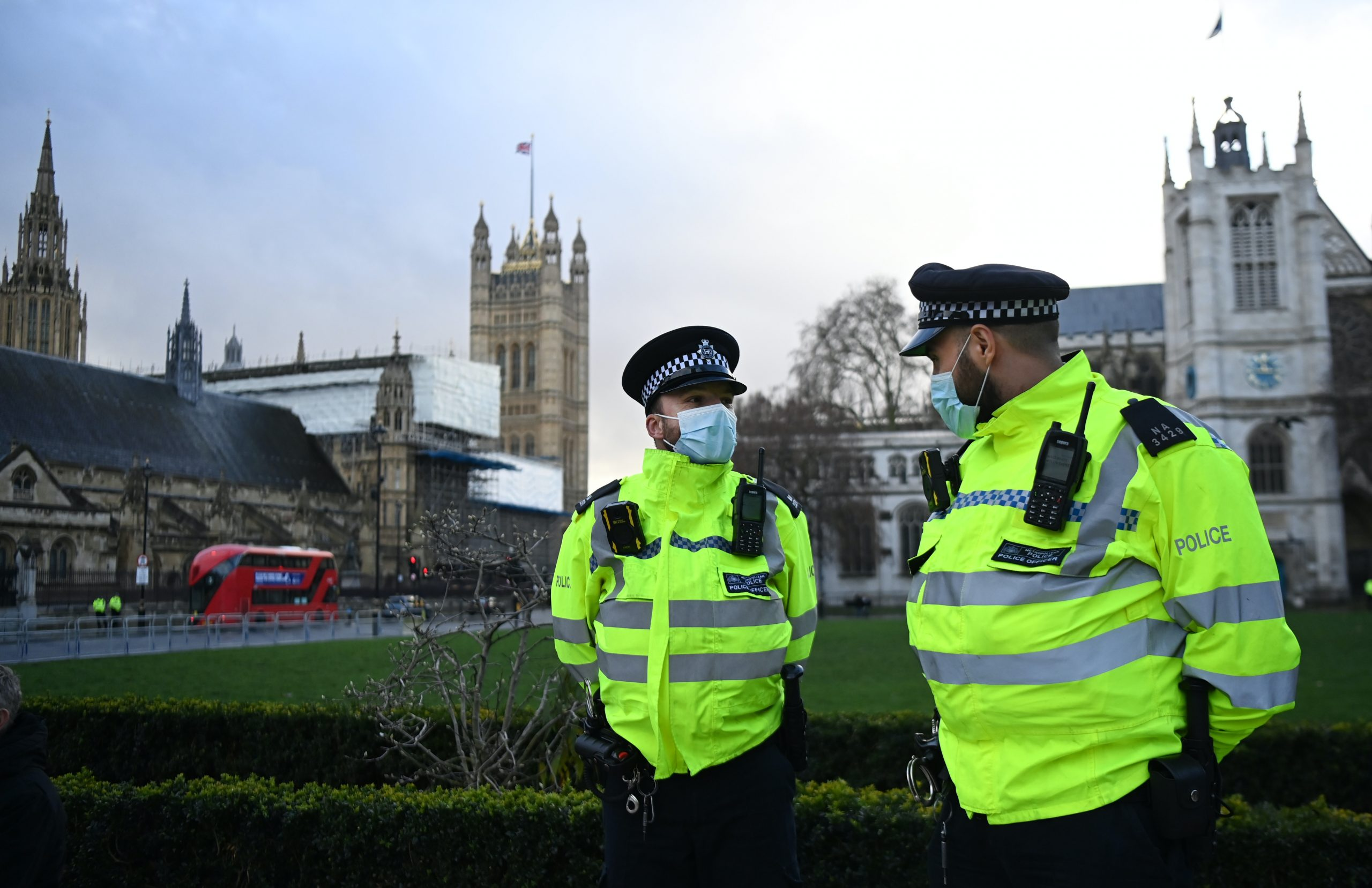 Two police officers wearing face masks standing outside with parliament in the background