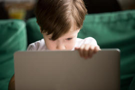 Curious kid boy secretly watching forbidden censored content on laptop