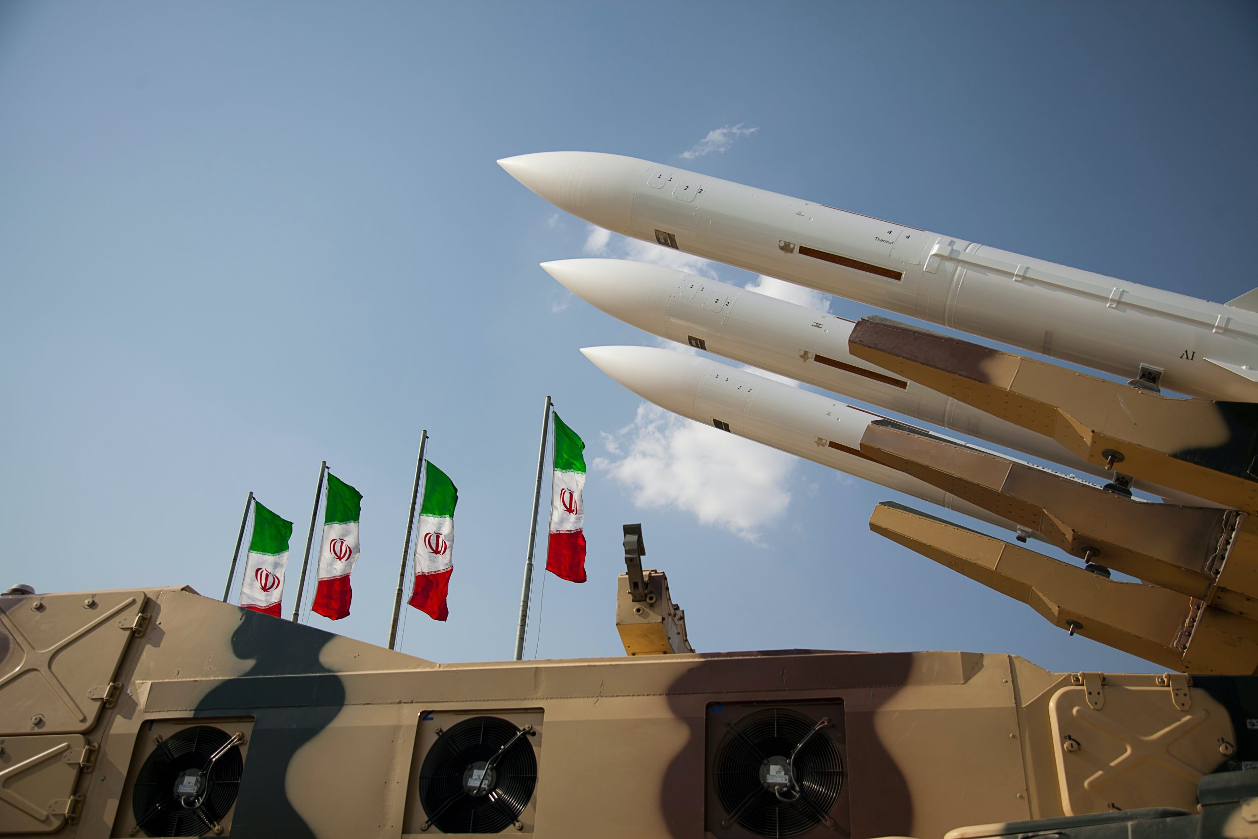 An array of missiles with Iranian flags in the background.