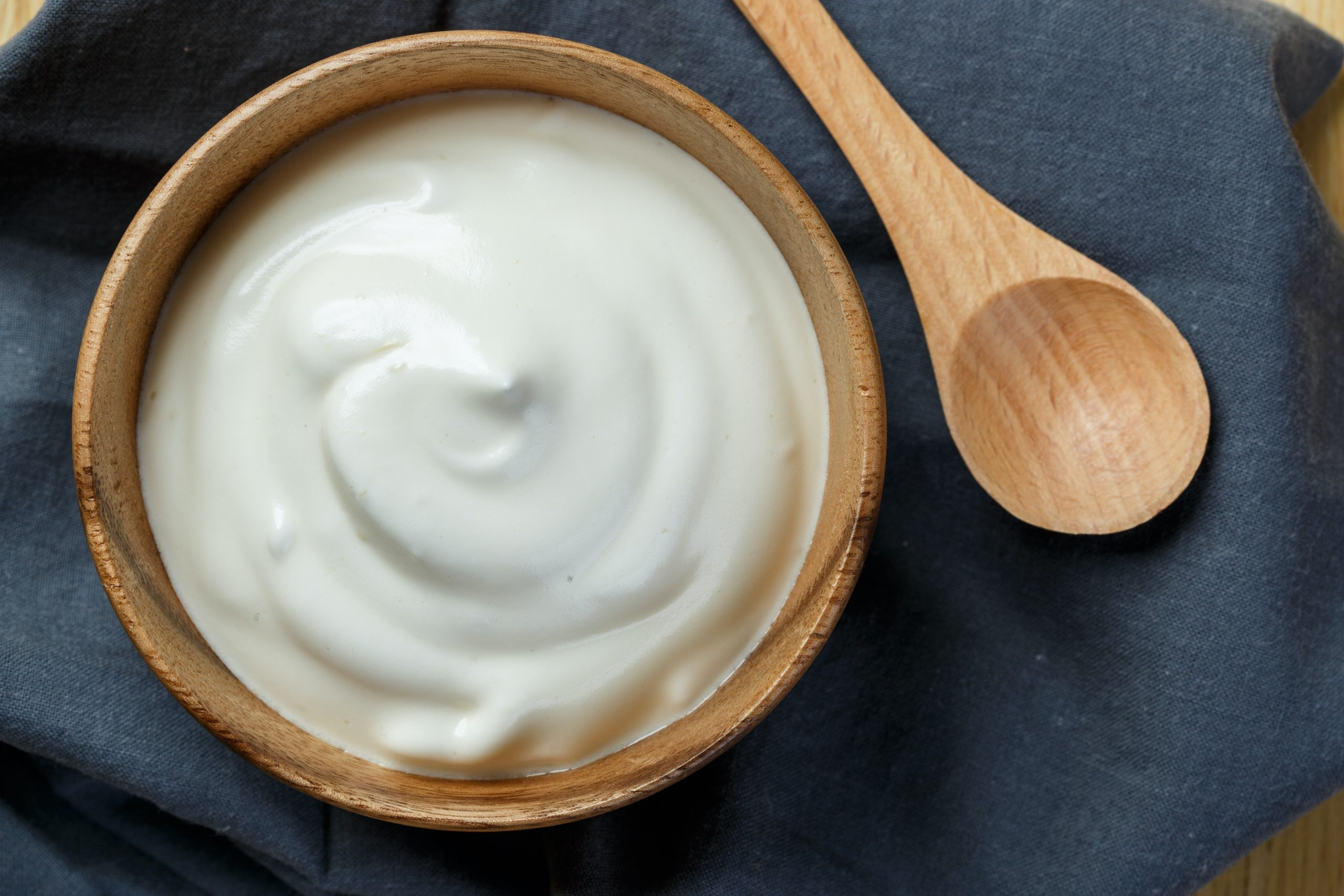Bowl of plain yoghurt with wooden spoon.