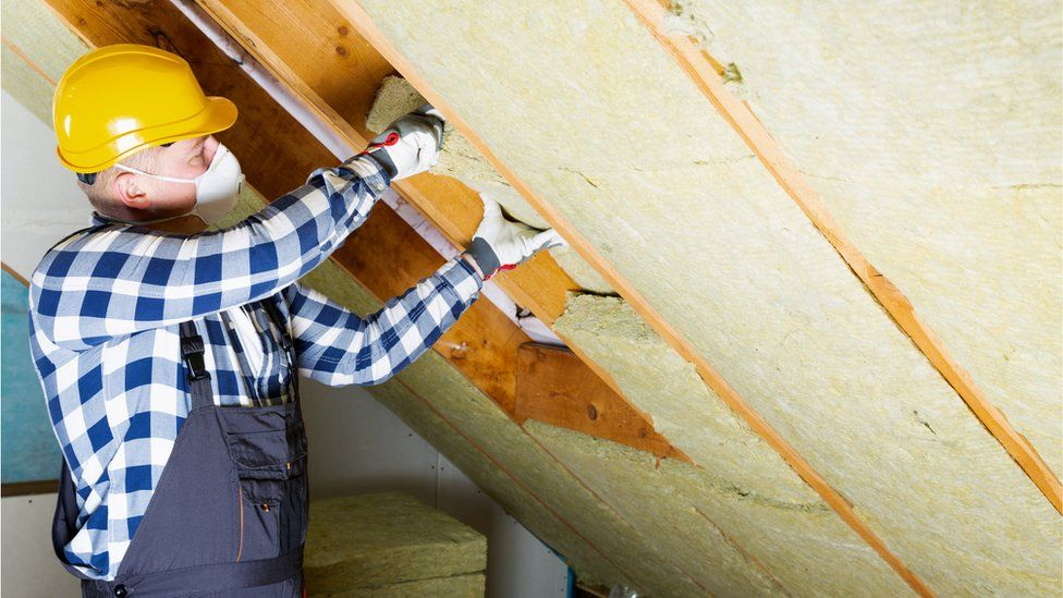 A builder installing thermal roof insulation