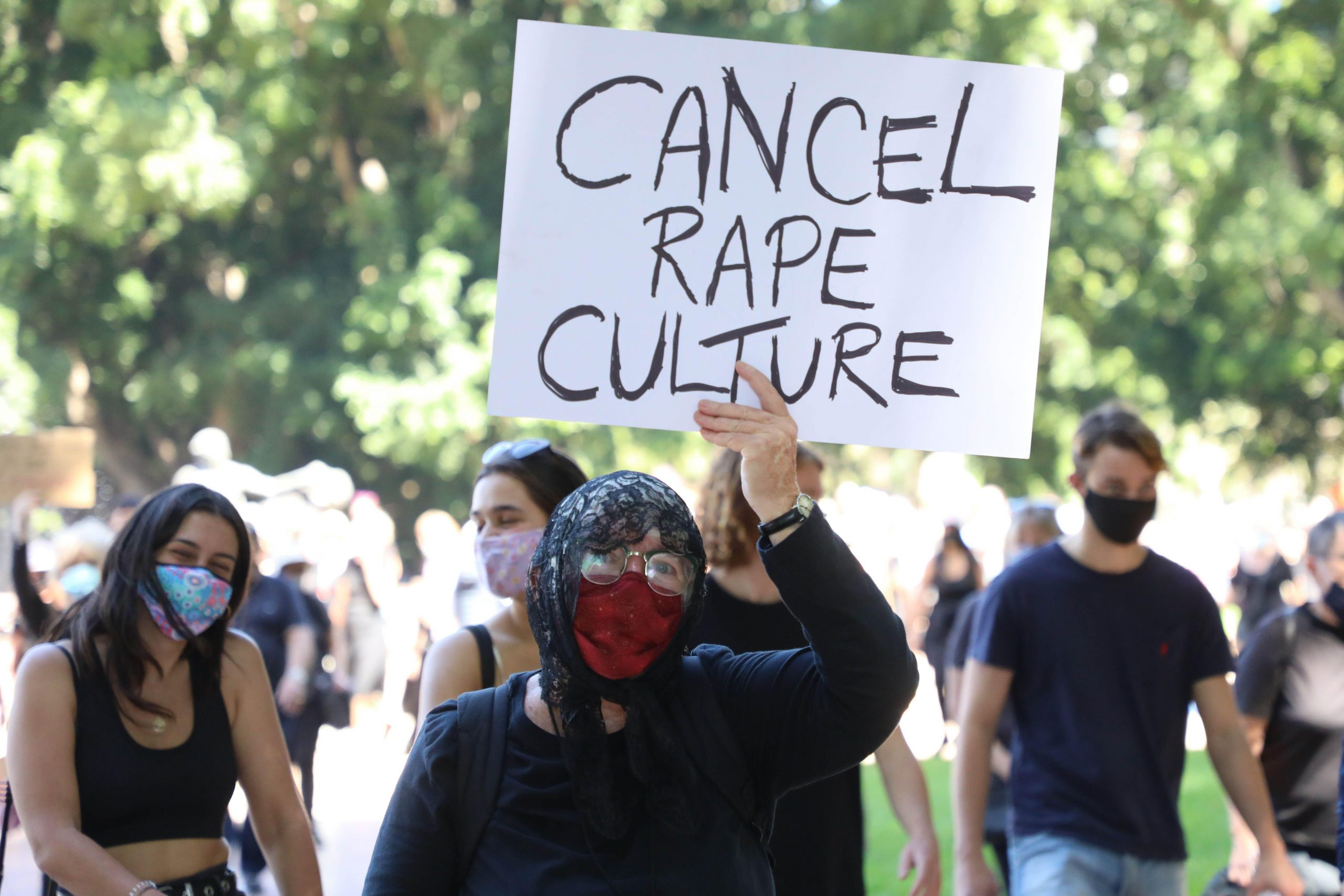 Masked protestor in black hoodie holds up card at protest that says 'CANCEL RAPE CULTURE'