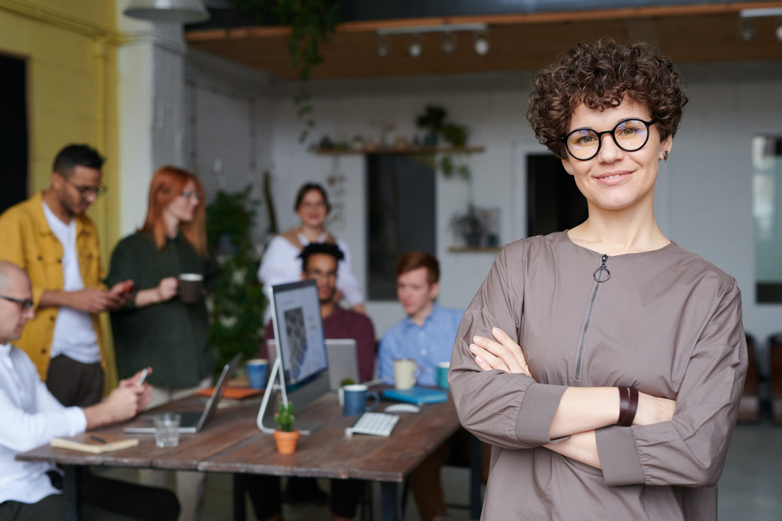 Office concept with woman wearing glasses in forefront.