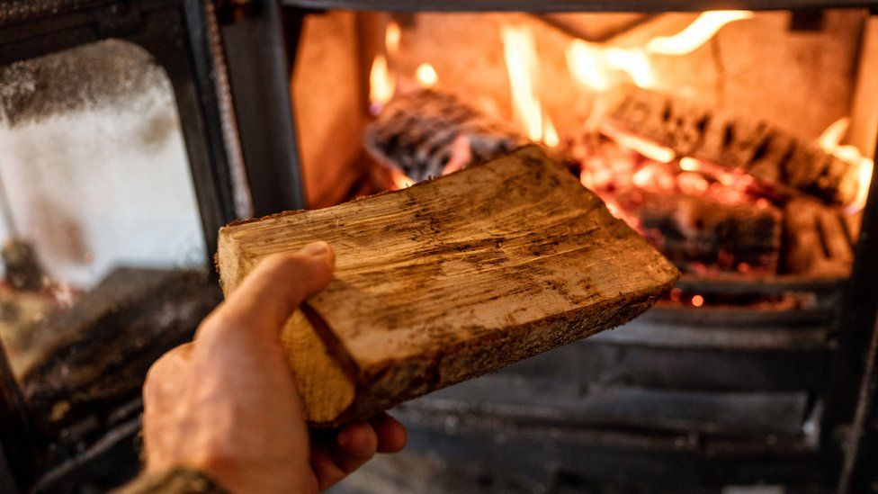 A log being put into a wood burning stove