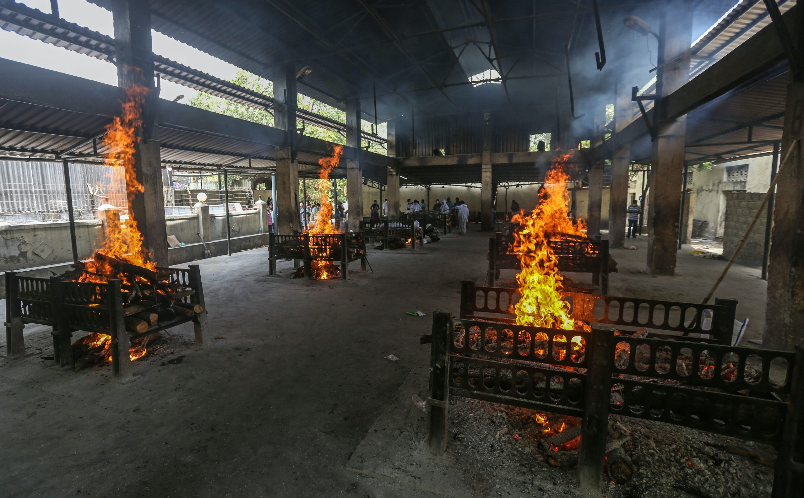 Piles of logs burn on small platforms positioned around a large, semi-open hall.