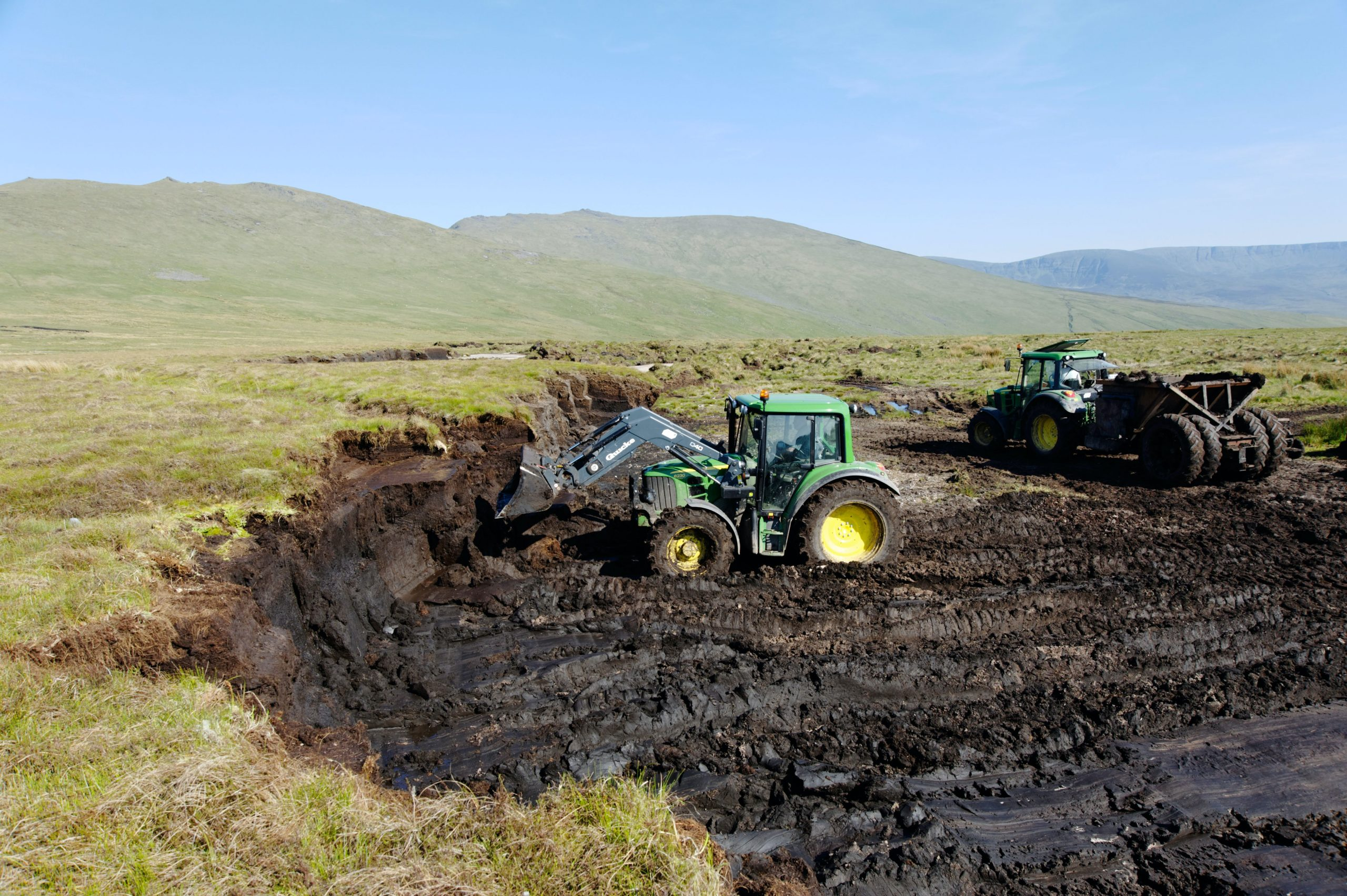 Tractors digging peat from within a bog crater.