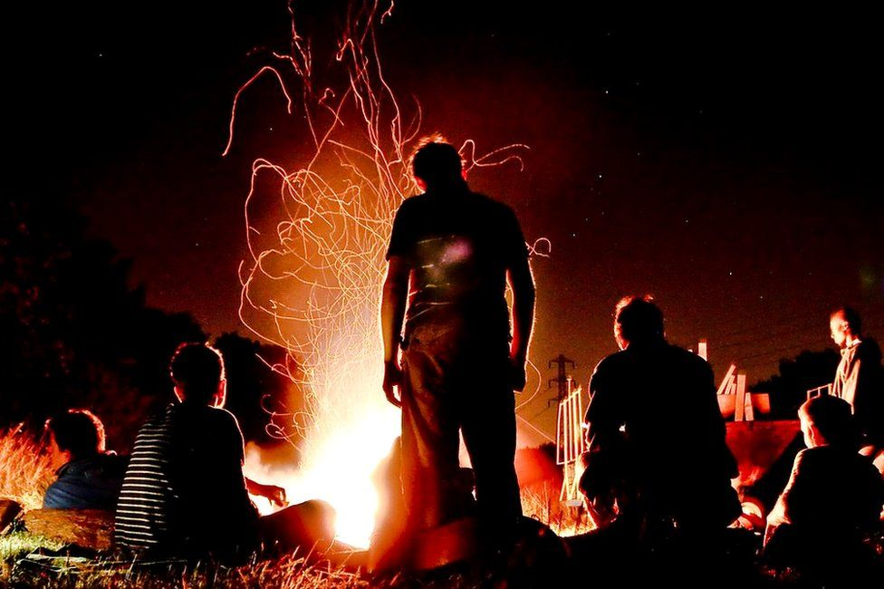 People gathered around a camp fire